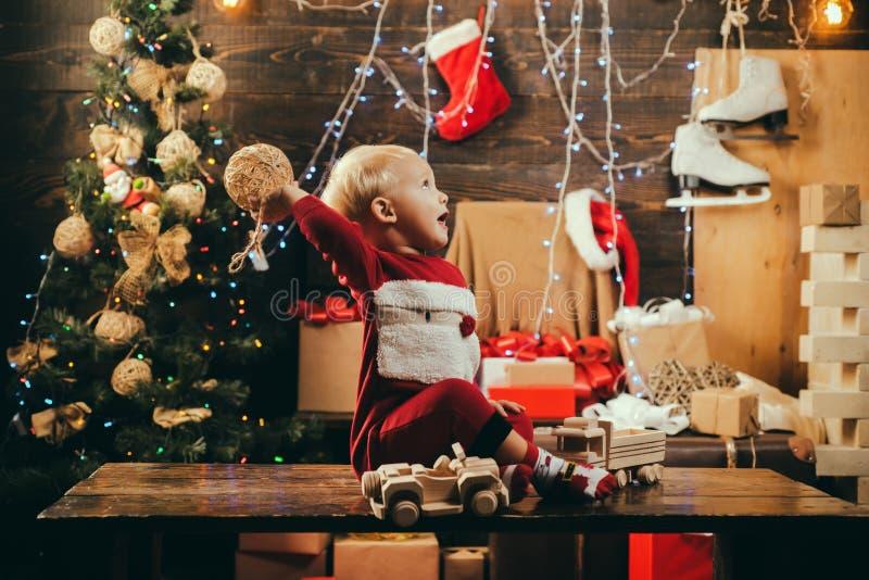 Infância do Natal Feliz Natal e ano novo feliz Bonito pouca criança no fundo da árvore de Natal O menino da criança imagem de stock royalty free