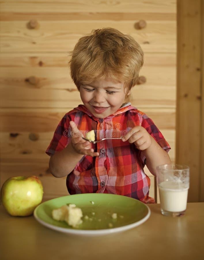 Infância e felicidade, independência dieta, vegetariano A criança pequena do menino come a banana e bebe o leite foto de stock