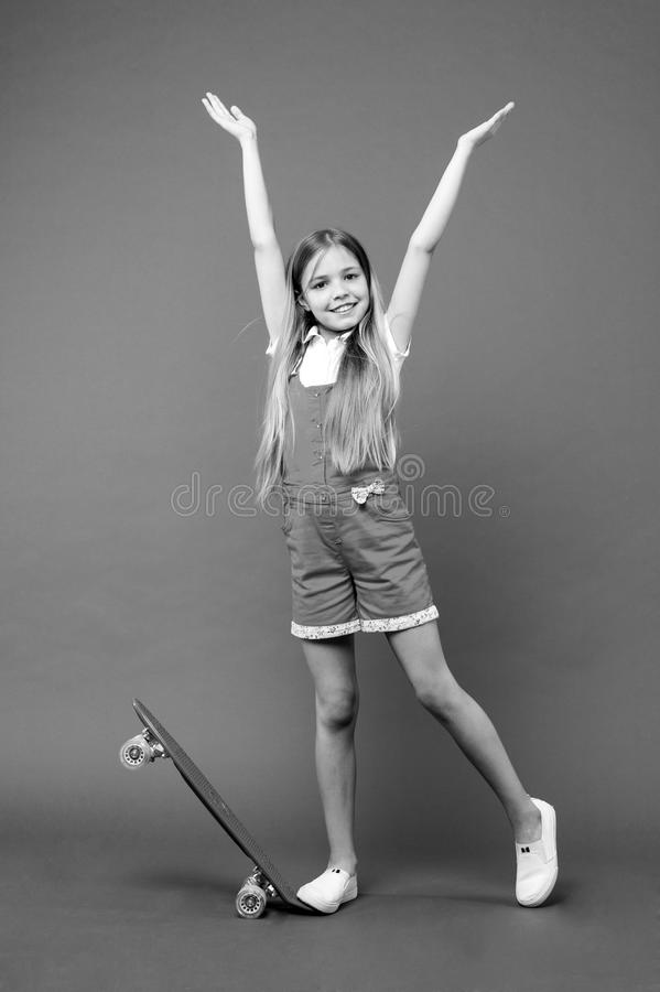 Infância e jogos ativos Sorriso pequeno da menina com placa do patim no fundo violeta Dia despreocupado Sorriso do skater da cria fotografia de stock