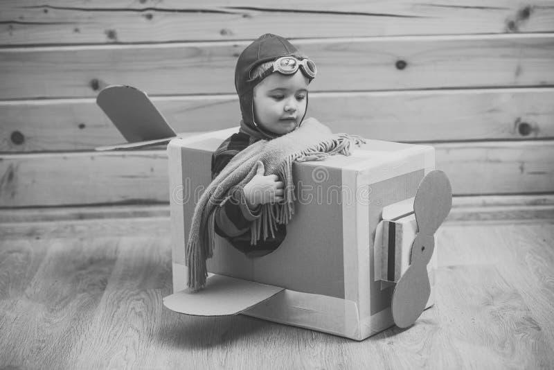 Infância Fantasia, imaginação Menino corajoso do sonhador que joga com um avião do cartão imagem de stock royalty free