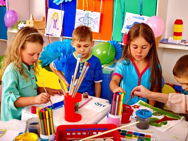 Infância feliz das crianças do grupo que pintam no jardim de infância fotografia de stock