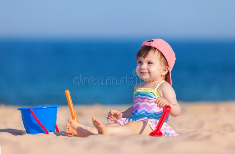 Infância feliz, férias em família felizes Criança bonito no fundo do mar Menina feliz que joga com a areia na praia do mar fotos de stock