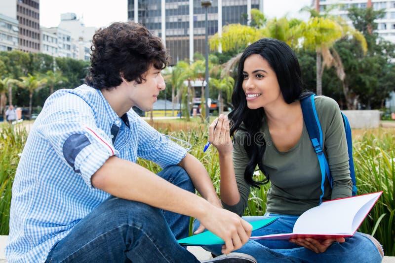 Infödd latin - amerikansk student som talar med vännen royaltyfri bild