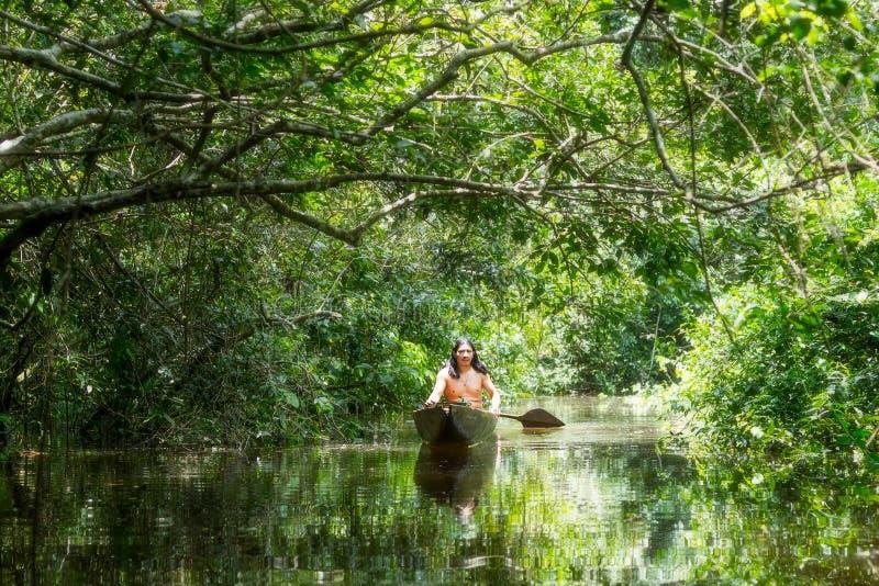 Infödd man med kanoten i amasonhandfat arkivbild