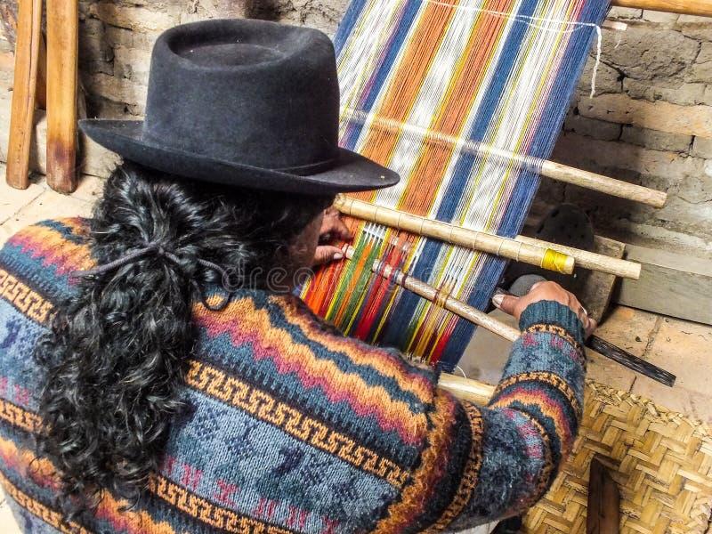 Infödd Quechua man som väver Handspun ull arkivfoton