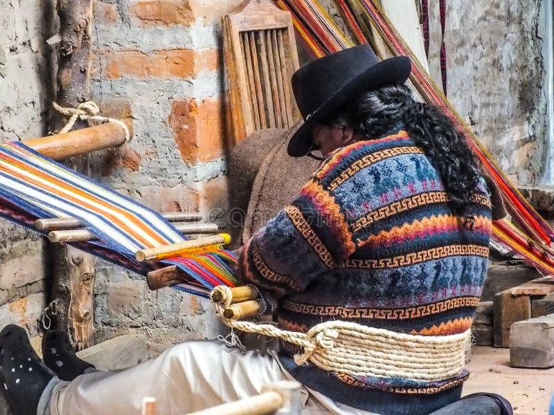 Infödd Quechua man som väver tyg på en Backstrap vävstol fotografering för bildbyråer