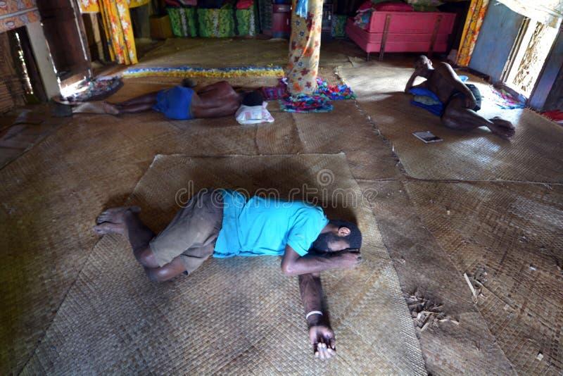 Infödda Fijianmän lägger slösat på golvet, når de har druckit mycket arkivbild