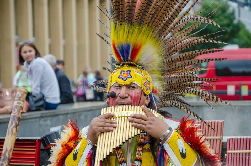 Infödda söder - amerikansk musiker som utför sång med pannaflöjten och bär den färgrika dräkten i gata av Prague royaltyfri foto