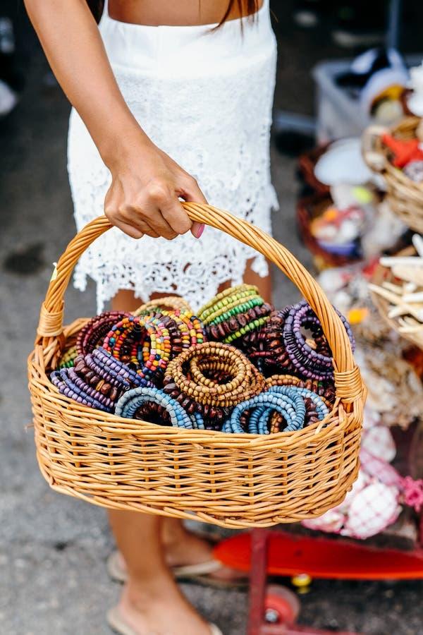Infödingen handcrafts färgrika armband i korgen Bärande korg för kvinnahand med mycket av handen - gjorda armband arkivfoton