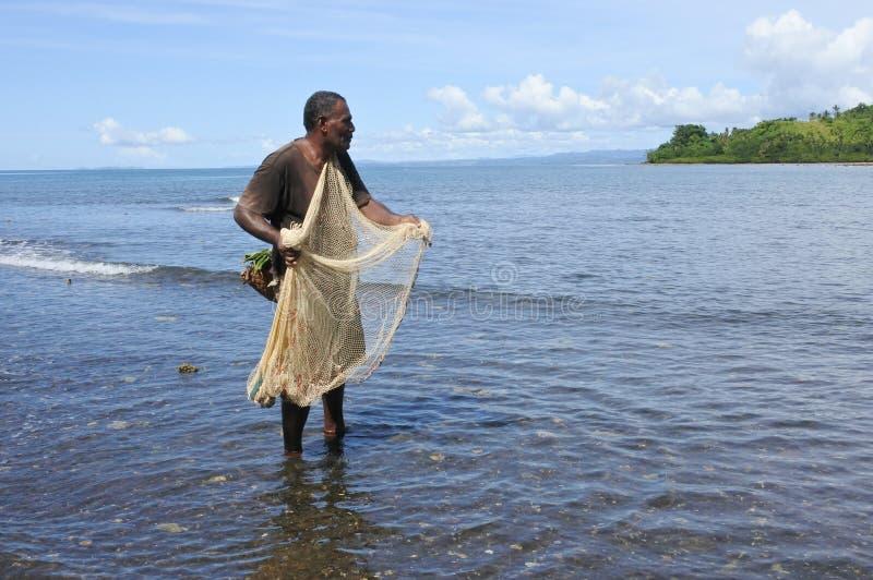Infött Fijianfiskarefiske med ett fisknät i Fiji arkivbild