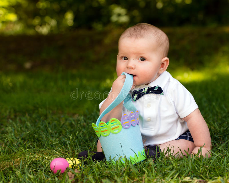 Infant baby boy playing with Easter eggs and basket. Cute infant baby boy playing with Easter eggs and basket royalty free stock photos