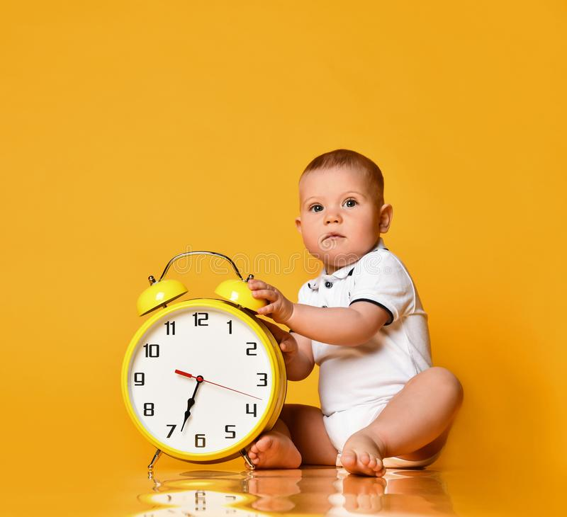 Infant baby boy toddler is occupied with sitting at big yellow alarm clock playing showing on yellow background royalty free stock photography