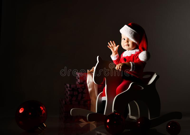 Infant baby boy toddler in red new year costume and Christmas cap is riding his wooden horse for children, waving at us stock photos