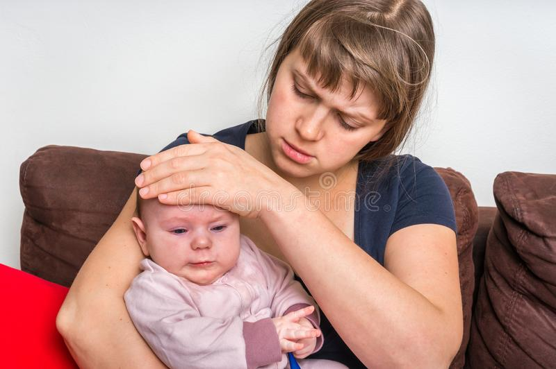 Infant baby with fever and worried mother with thermometer stock image