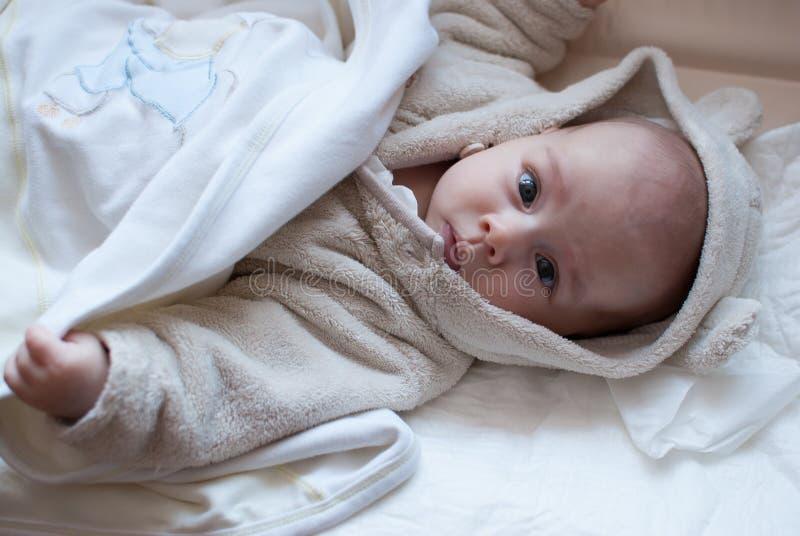 Infant baby girl in bed getting to sleep in bathrobe. Infant baby girl in bed getting to sleep in bear bathrobe stock photo