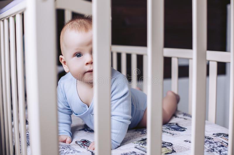 A small child lies in a baby crib and looks at the camera. An infant baby lies in a baby crib and looks at the camera stock image