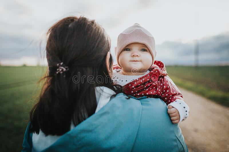 Infant baby looks over mothers shoulder - autumn outdoor family lifestyle concept royalty free stock photo