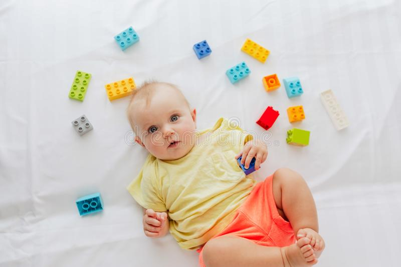 Infant baby lying on white bed stock photography
