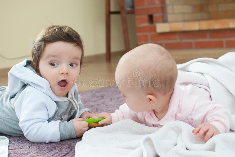 Infant boy and girl on the floor stock photography