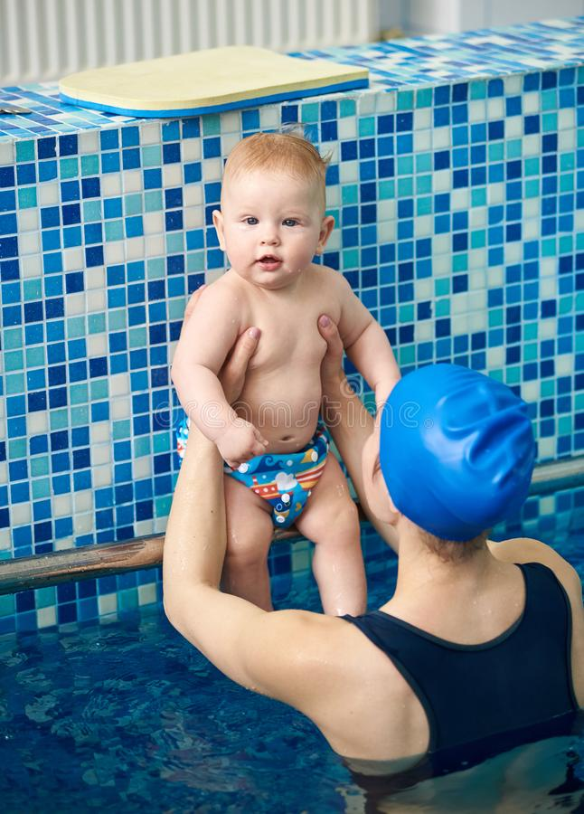 Infant boy looking in camera, active time resting with mother in paddling swimming pool. Mom preparing future swimmer royalty free stock images