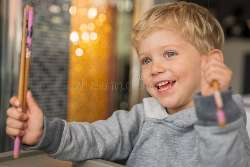 Infant boy smiling with chopsticks at restaurant stock photo