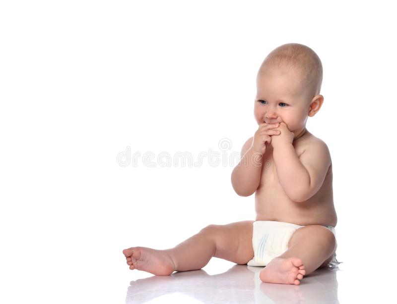 Infant child baby boy in diaper is sitting on the floor holding both his hands in his mouth on white. Infant child baby boy toddler in diaper is sitting on the royalty free stock image