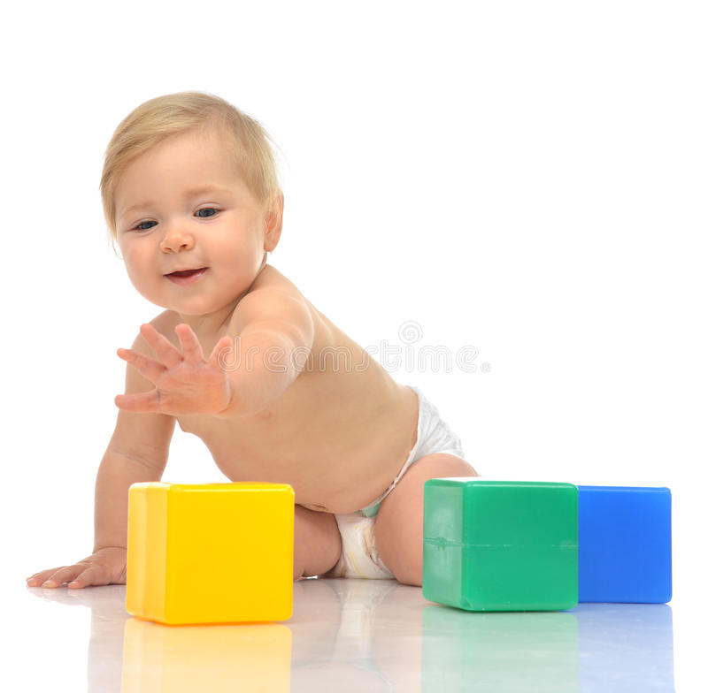 Infant child baby boy toddler playing holding green blue yellow. Bricks in hands on a floor on and looking up isolated a white background royalty free stock images
