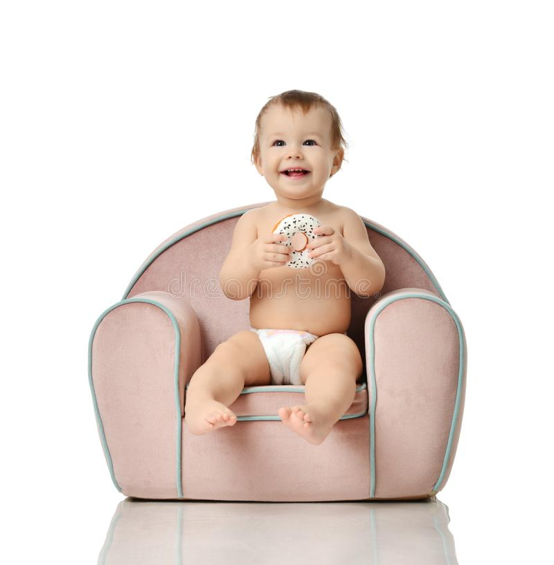 Infant child baby girl kid toddler in diaper sit in little armchair chair eat donut stock photography