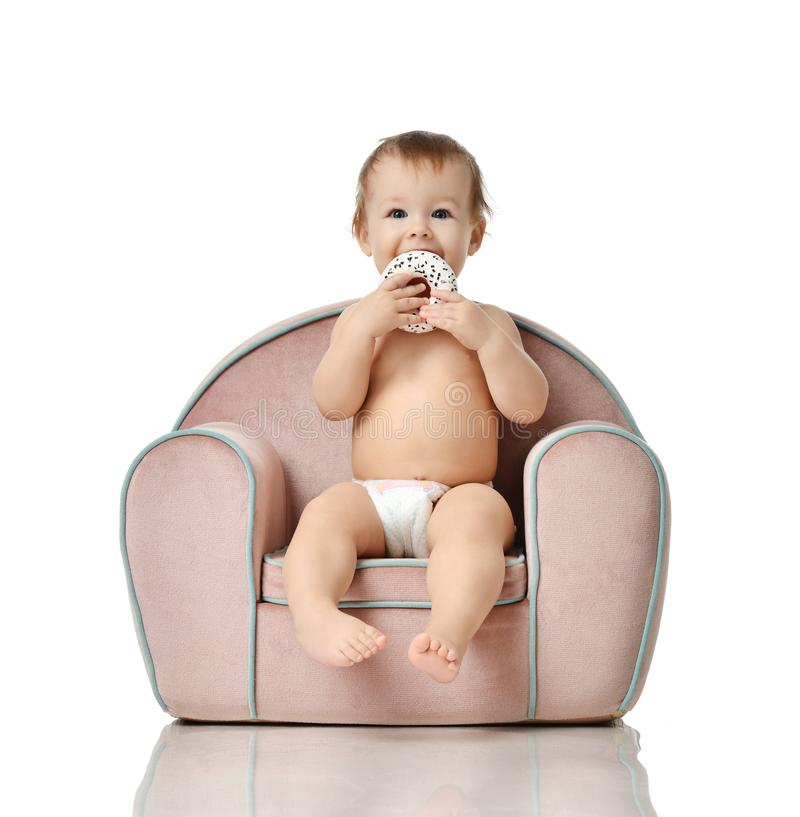 Infant child baby girl kid toddler in diaper sit in little armchair chair royalty free stock image