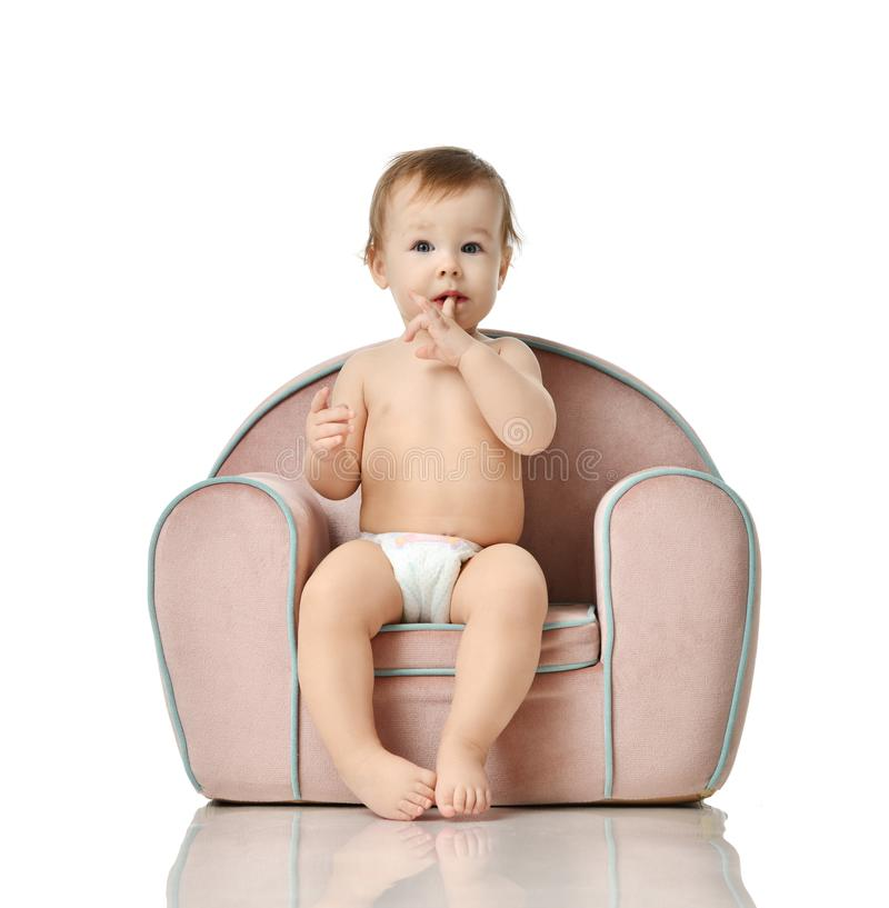 Infant child baby girl kid toddler in diaper sit in little armchair chair stock images