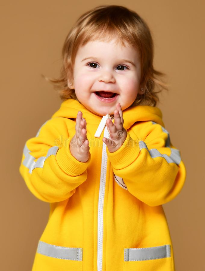 Infant child baby girl kid toddler in winter yellow overalls clap her hands happy smiling on brown stock photography