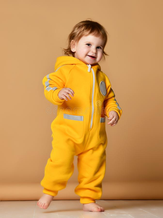 Infant child baby girl kid toddler in winter yellow overalls make first steps happy smiling. On grey background stock photo