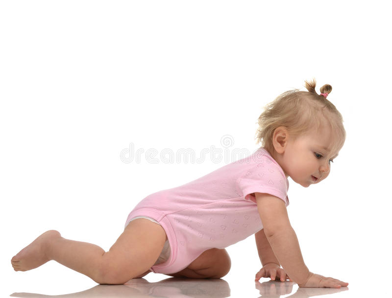 Infant child baby girl toddler crawling happy looking straight. Isolated on a white background royalty free stock image