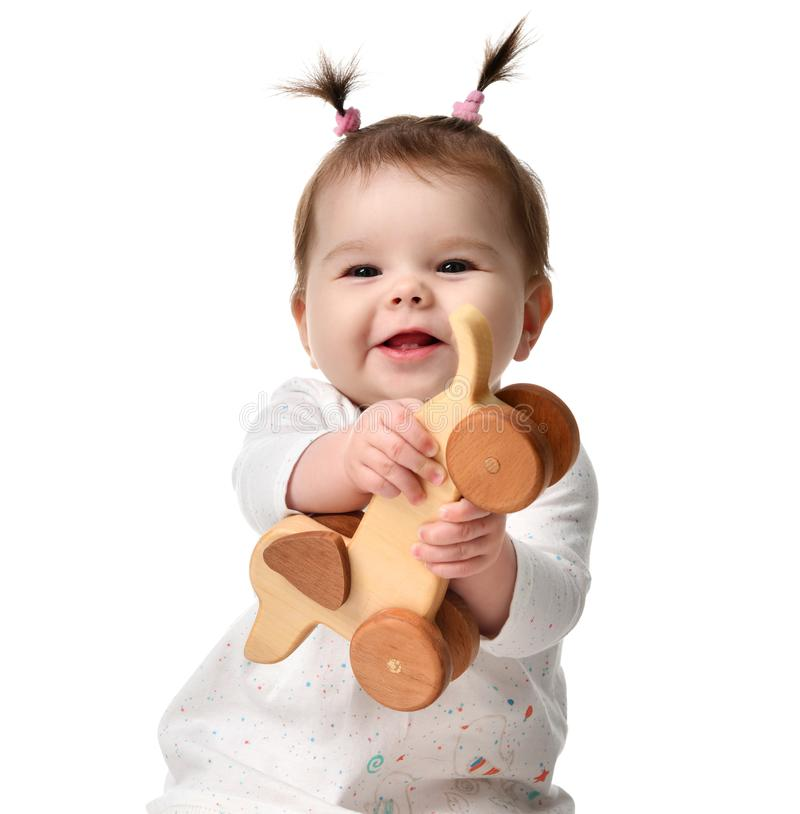 Infant child baby girl toddler sitting playing with eco wood dog toy happy smiling royalty free stock photography