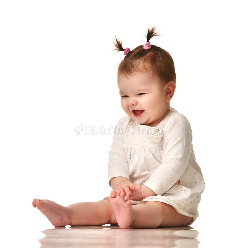 Infant child baby girl in white dotted dress sitting happy laughing smiling isolated on a white. Background stock photos