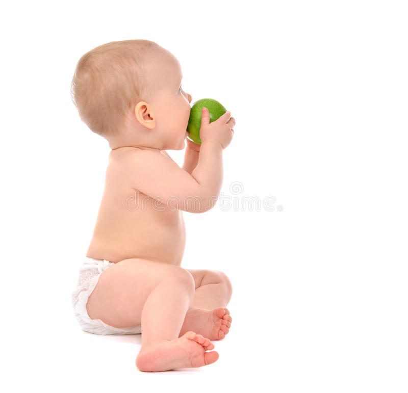 Infant child baby infant girl eating apple closeup. Infant child baby infant girl eating green apple closeup isolated on a white background stock photo