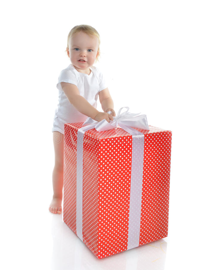 Infant child baby toddler kid with big red present gift for birthday. Or new year celebration isolated on a white background Christmas new year concept stock photography