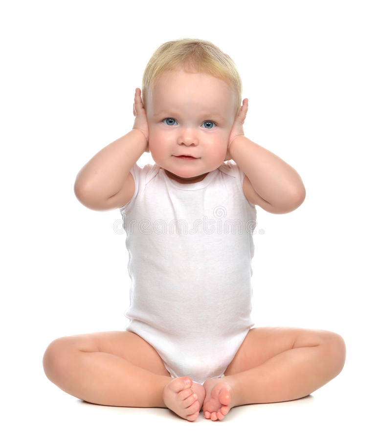 Infant child baby toddler sitting closed her hands over ears and royalty free stock image