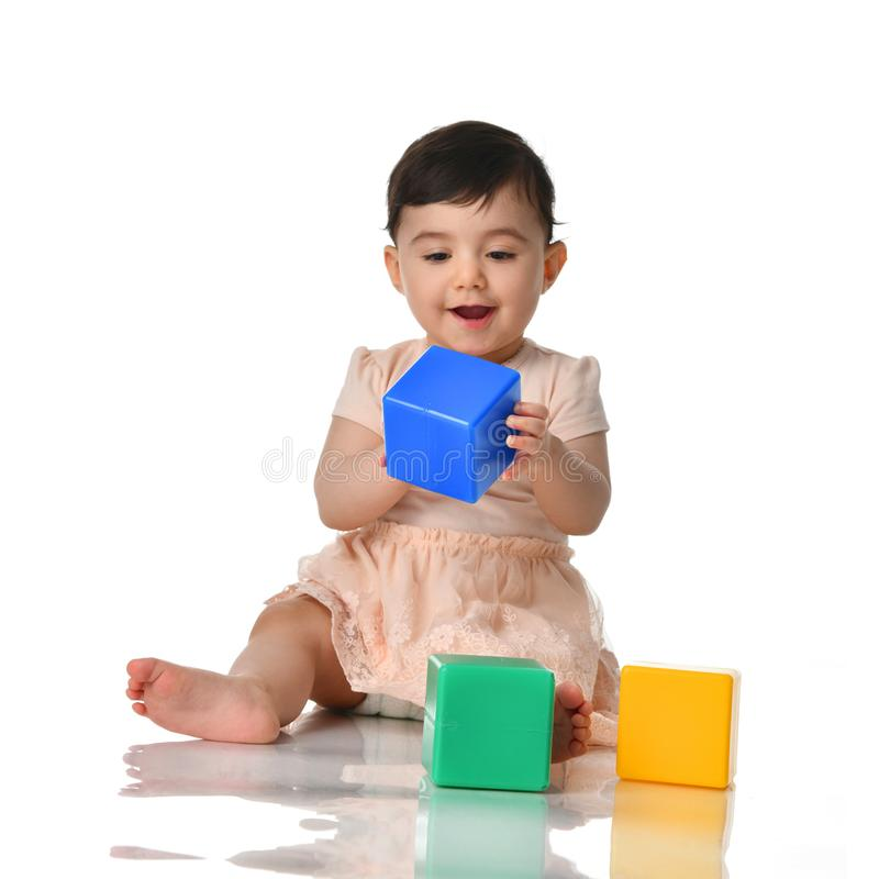 Infant child baby toddler sitting in dress with green blue and yellow brick toy playing isolated on a white. Background royalty free stock photography