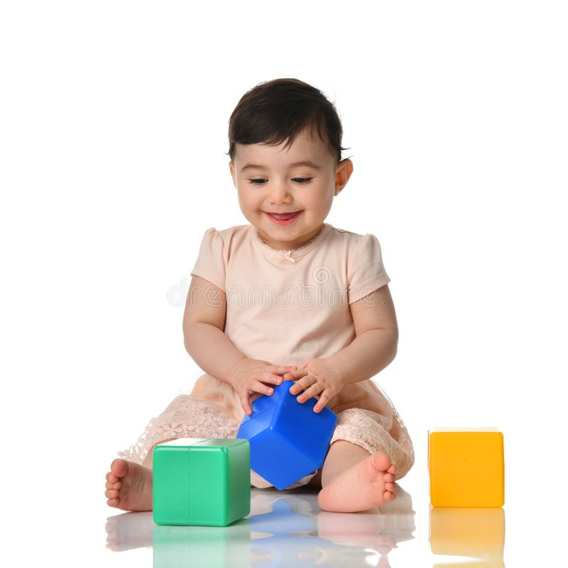 Infant child baby toddler sitting in dress with green blue and yellow brick toy playing on a white. Background royalty free stock photo