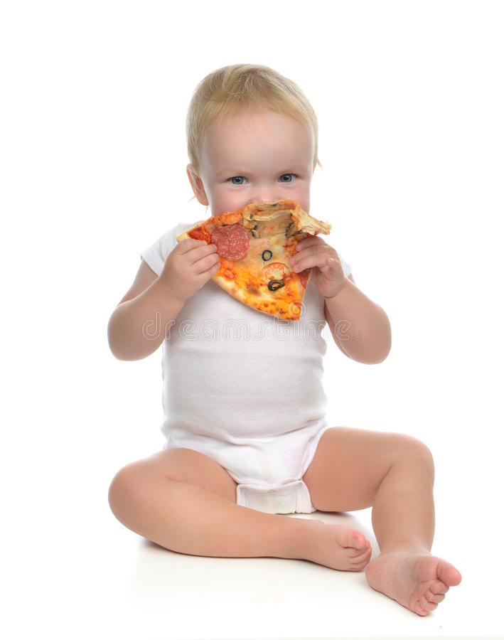Infant child baby toddler sitting enjoy eating slice of pepperoni pizza stock photography