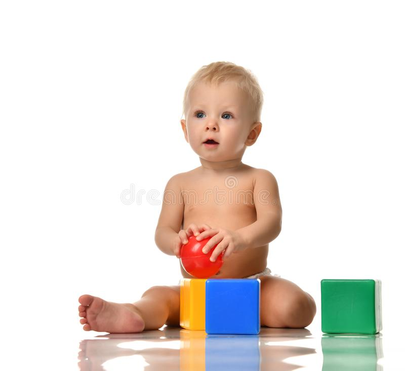 Infant child baby toddler sitting naked in diaper with green blue brick toy and red ball playing royalty free stock photography