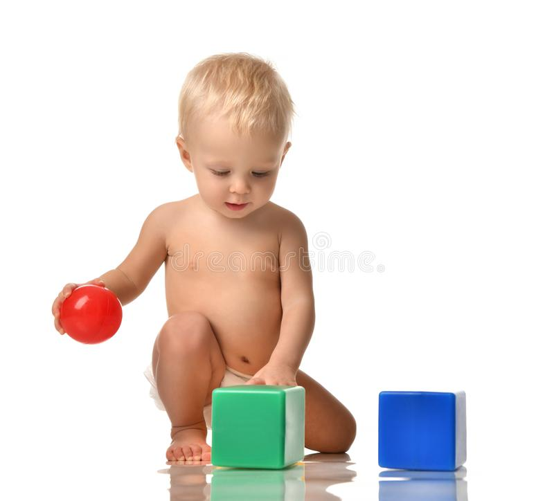 Infant child baby toddler sitting naked in diaper with green blue brick toy and red ball playing royalty free stock photos