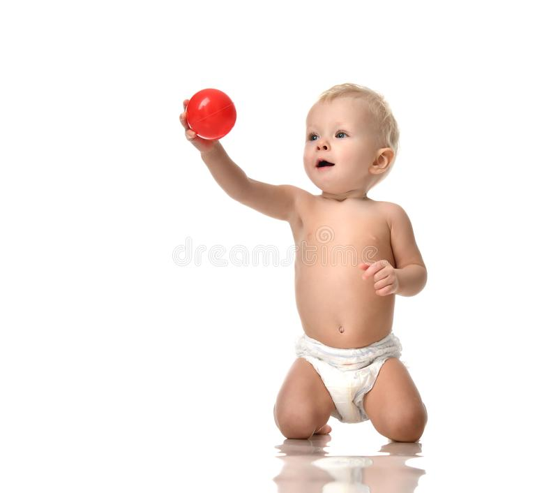 Infant child baby toddler sitting naked in diaper and play with red ball isolated stock photos