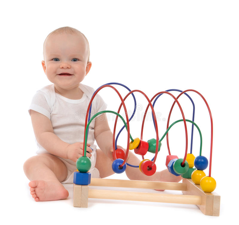 Infant child baby toddler standing and playing wooden educational toy. With looped wires for teaching coordination on a white background royalty free stock photos