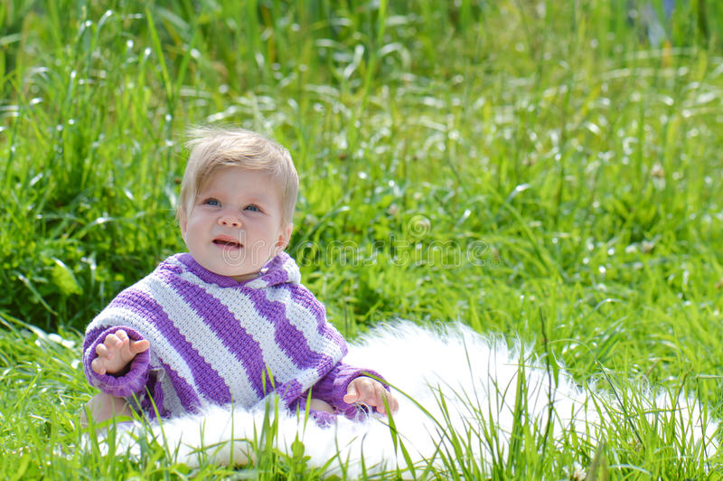 Infant child in the park. Baby girl in poncho in the park on the grass royalty free stock photo