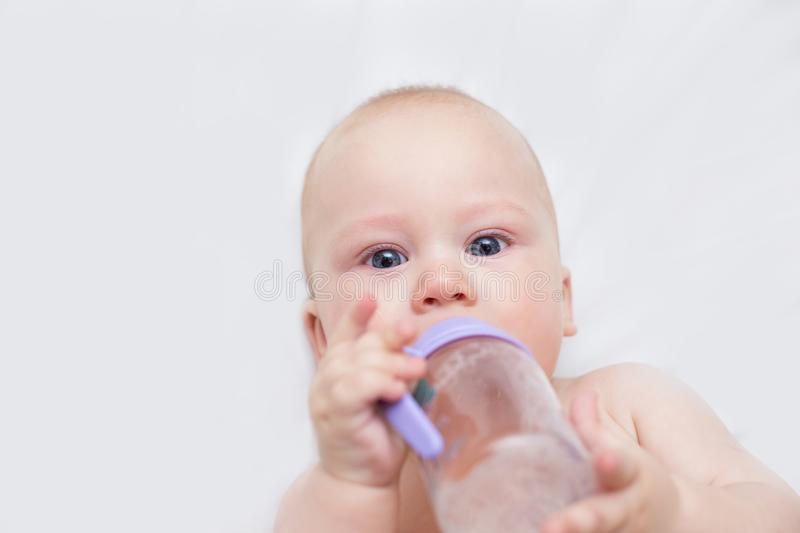 Infant is drinking from a bottle and lying stock image