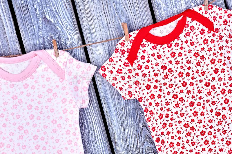Infant girl clean clothes on rope. Baby girl cute cotton apparel hanging on clothesline on wooden background, top view royalty free stock photos