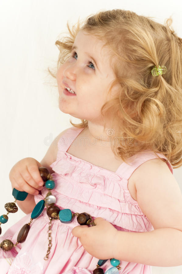 Infant girl holding a large bead necklace. stock image