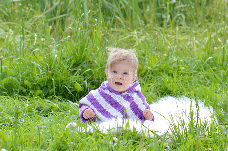 Infant girl in a poncho. Child in the park on the grass royalty free stock images